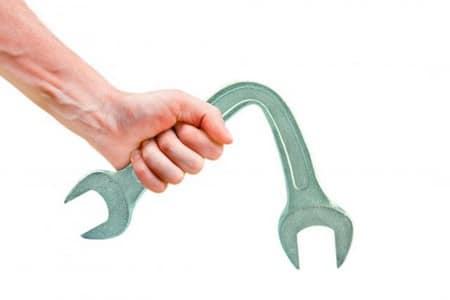 Согнутый гаечный ключ в руке