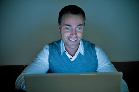Мужчина смотрит на экран ноутбука