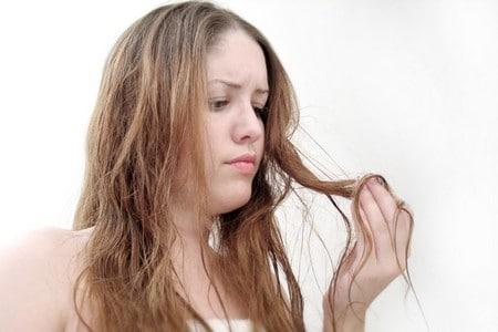 Женщина осматривает свои волосы