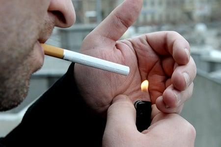 Мужчина поджигает сигарету