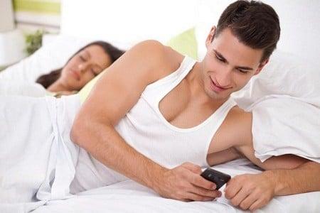 Мужчина в кровати с мобильным телефоном