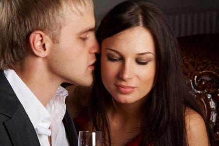 Мужчина шепчет девушке на ухо