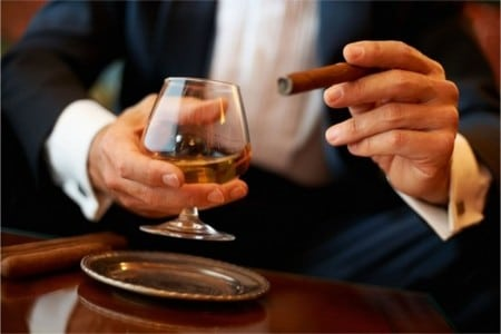 Мужчина держит бокал коньяка и сигару