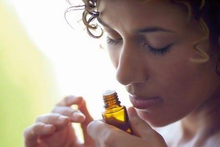 Женщина нюхает баночку с маслом
